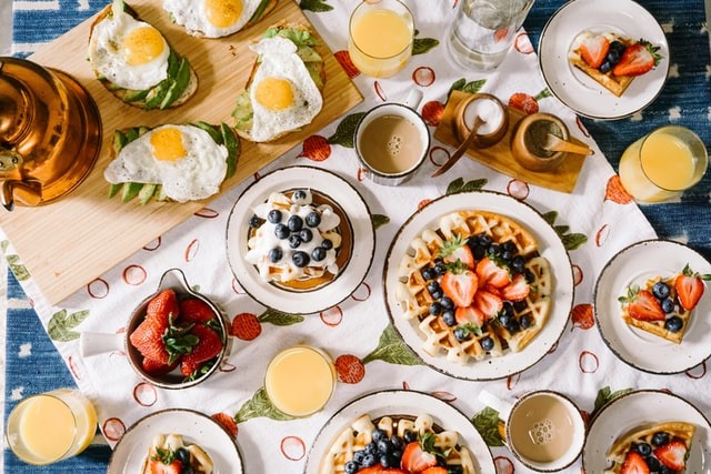 Waffles, juices, toast along with other breakfast items on the table -daily routine of a student in English